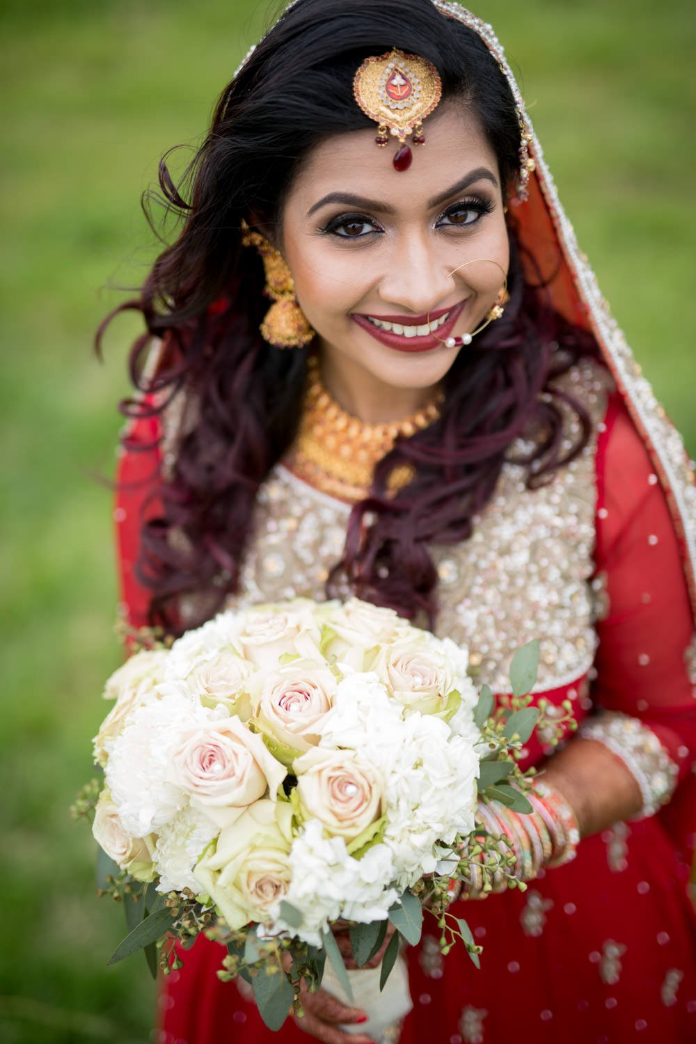 Bengali bride genuinely smiling during her bridal portraits on her wedding.