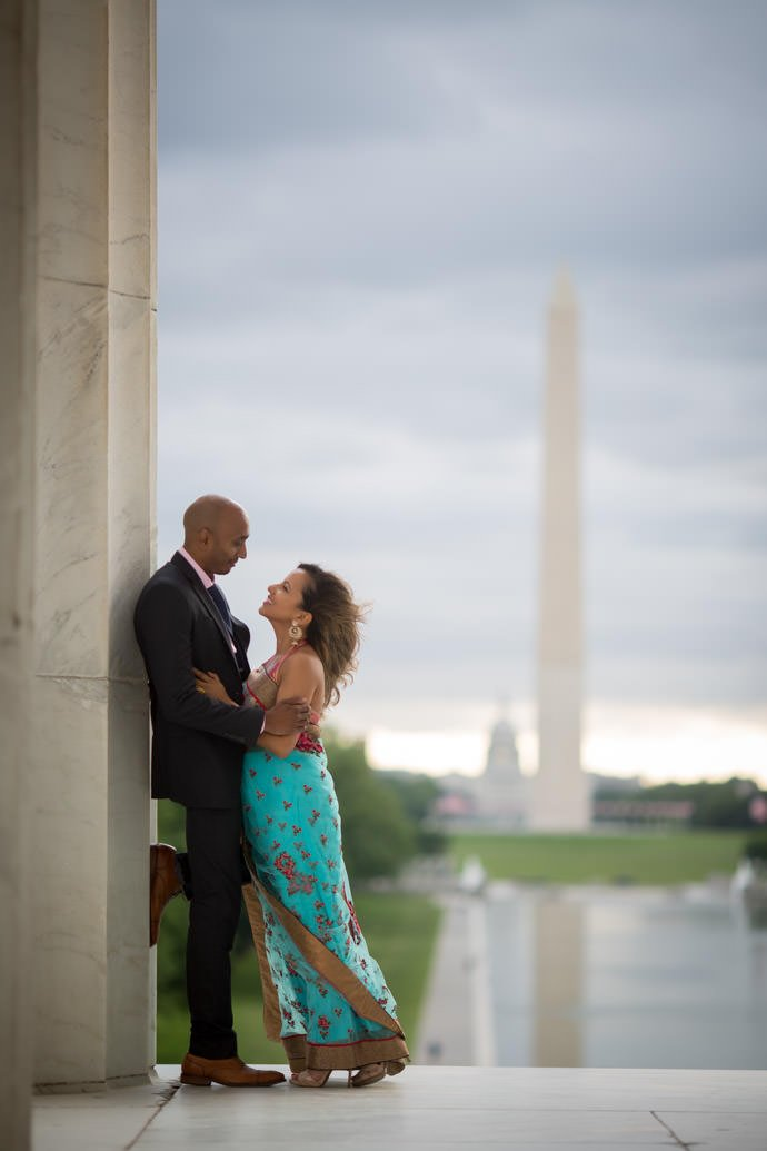 A Indian and Nepali couple posing for a photograph at the Lincoln Memorial with the Washington Monument in the background in Washington D.C.