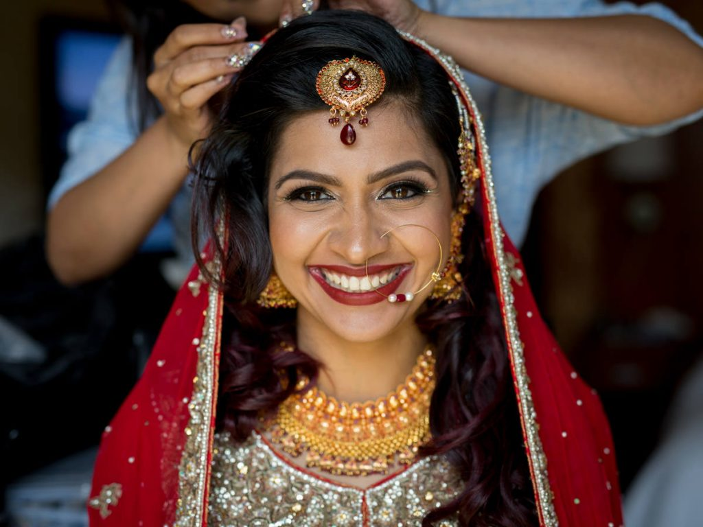 A Bengali bride smiles as she finishes getting ready for her wedding at Foxchase Manor in Manassas, Virginia.