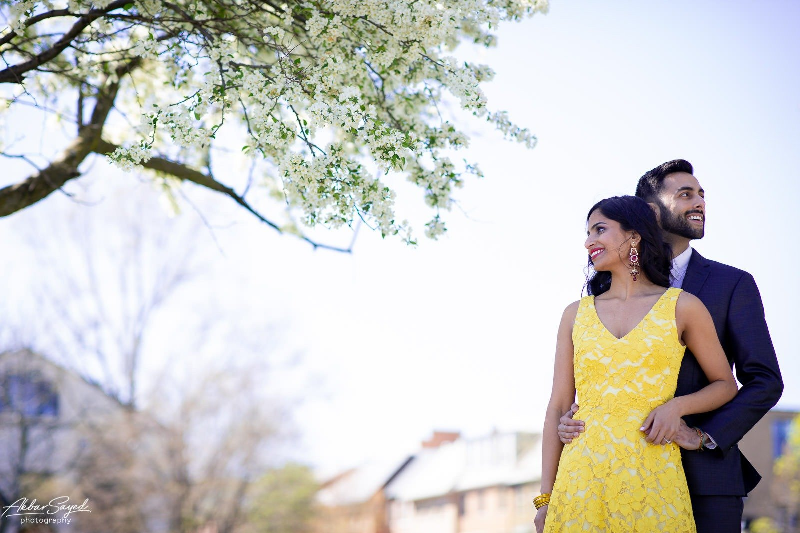 Old Town Alexandria engagement photo with an engaged Indian - American couple in front of a bush in bloom with bright white flowers.