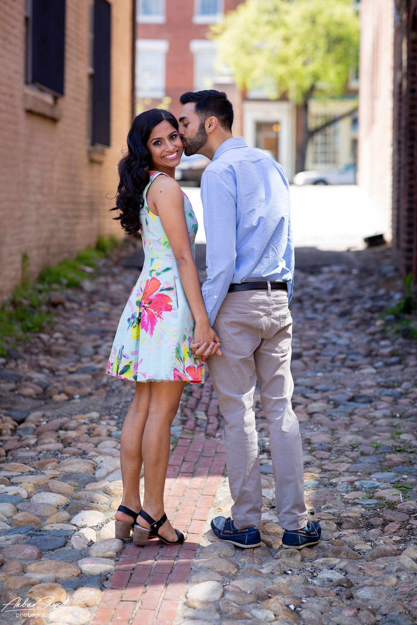 Old Town Alexandria engagement photo with an engaged Indian - American couple in a cobblestone alley.