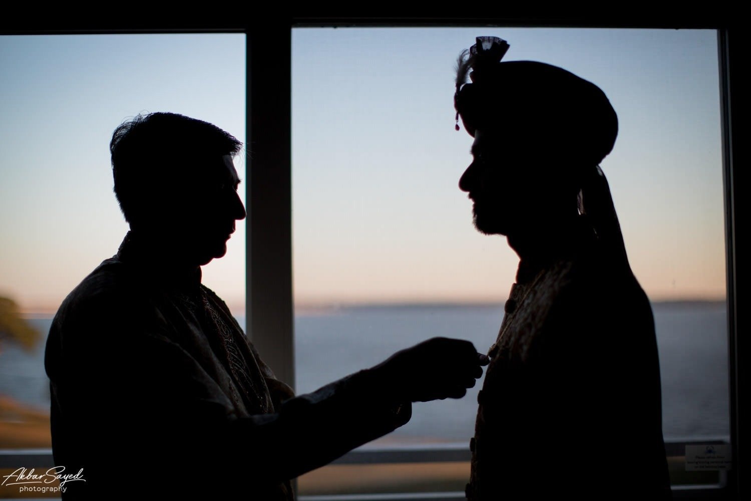 A photo of a Indian groom getting ready with his father during a Jewish - Hindu fusion wedding at the Chesapeake Bay Hyatt in Cambridge, Maryland.